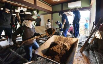 広島県熊野町で住宅内に流れ込んだ土砂を取り除くボランティアや近所の人たち=14日午後1時1分