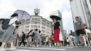 厳しい暑さの東京・銀座で日傘を差して歩く女性=14日午前