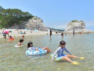 青空の下、海水浴を楽しむ子どもたち。県内は梅雨明けを待たずに真夏の暑さが続きそうだ=14日、宮古市・浄土ケ浜