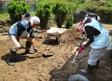 民家の裏に流れ込んだ泥を取り除くボランティアたち(14日午前10時56分、京都府福知山市上大内)
