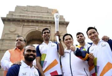 15日、インドの首都ニューデリーにある観光名所「インド門」周辺を回ったアジア大会の聖火(共同)
