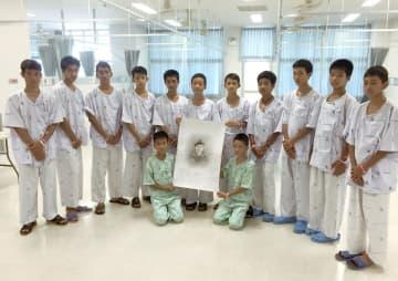 死亡した元海軍特殊部隊員の顔が描かれた紙を囲む、救出された少年ら(タイ保健当局提供、共同)