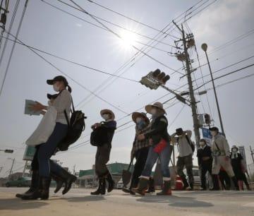 強い日差しの下、支援活動に向かうボランティアら=15日午前9時11分、岡山県倉敷市真備町地区