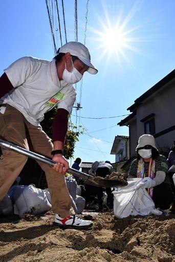 厳しい日差しが照りつける中、土砂の撤去を手伝うボランティア(15日午前9時21分、広島市安芸区矢野西5丁目)