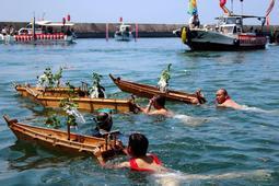 沖に向かって小舟を押し進める氏子ら=明石市港町