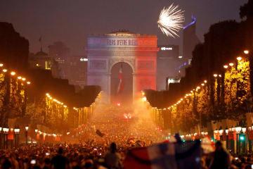 15日、凱旋門がフランス国旗の「青白赤」にライトアップされたパリ中心部シャンゼリゼ通りで、サッカーW杯の優勝を祝うファンら(ロイター=共同)
