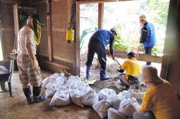 水路があふれて浸水した建物で土砂のかき出し作業に励む住民やボランティア=15日、丹波市市島町徳尾