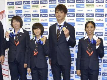 帰国し、メダルを手にポーズを取る田中希実(中央左)と橋岡優輝(同右)ら=17日午前、成田空港