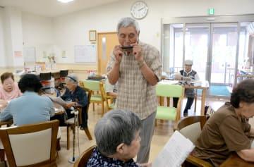 通算700回目となる訪問演奏で、ハーモニカを奏でる江藤秀樹さん=9日、益城町