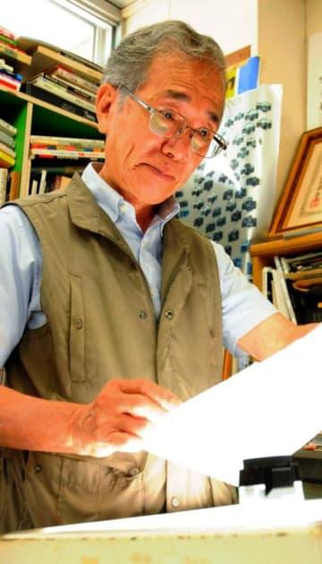 父・山田實さんの個展の出品カットをネガから探す勉さん=那覇市久米
