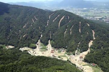 尾根付近から土砂が崩れ落ちた跡が幾筋も延びる呉市東部の山(12日午後0時33分)