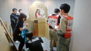 避難所で段ボール製更衣室を組み立てる長岡市の職員ら=11日、岡山県高梁市