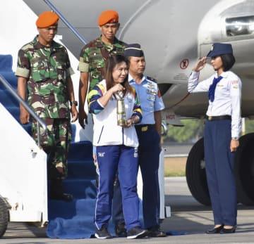 聖火の入った容器を手に持つインドネシアのバドミントン五輪金メダリスト、スシ・スサンティさん(中央)=17日、ジョクジャカルタ(共同)