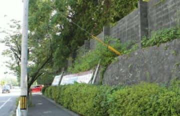石垣の上にブロック塀がある別府鶴見丘高校。「危険」として今月中に撤去作業に入る=17日、別府市鶴見