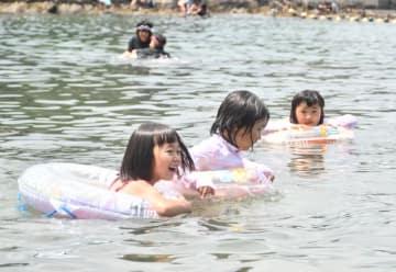 浮輪に乗って波間に浮かぶ子どもたち