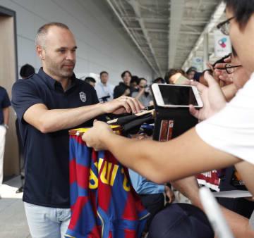 関西空港に到着し、ファンのサインの求めに応じるJ1神戸のアンドレス・イニエスタ選手(左)=18日午前