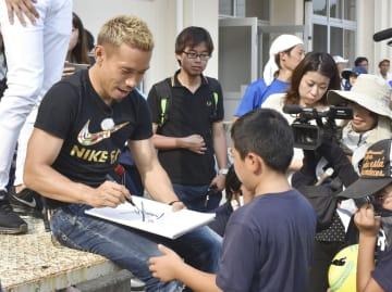 豪雨被害を受けた愛媛県大洲市で小学校を訪問し、児童らにサインするサッカー日本代表の長友佑都選手=18日午後