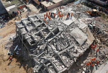 18日、インド・グレーターノイダのビル倒壊現場で生存者を探す救助関係者ら(ロイター=共同)