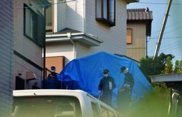遺体発見現場となった鷹仁容疑者の実家を調べる県警捜査員=18日、茨城県取手市