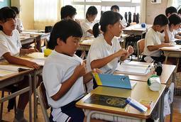 襟元をつまんで服の中に風を入れる児童=18日午後1時57分ごろ、姫路市立城北小学校