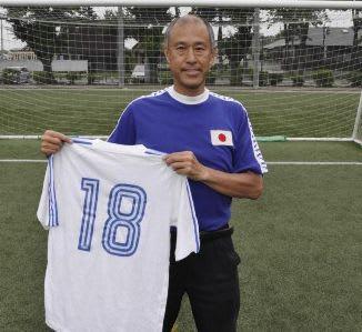 西野監督が1978年の日本代表選出時に身に着けたユニホームを掲げる坂上さん