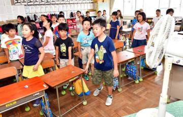 汗をかきながら、扇風機が設置された教室での授業に臨む桜城小の児童=18日、盛岡市大通