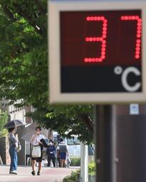 街の温度計が「37度」を表示する猛暑の中、日傘を差して歩く女性ら=19日午後4時7分、神戸市須磨区須磨本町2(撮影・吉田敦史)