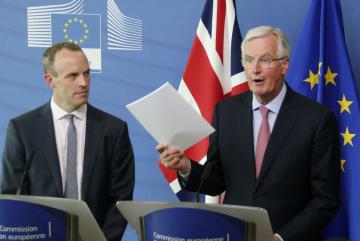 離脱協定案のコピーを手に記者団に話すEUのバルニエ首席交渉官。左は英国のラーブEU離脱担当相=19日、ブリュッセルのEU本部(共同)