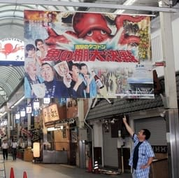 新作映画の告知ポスターのような巨大看板を取り付ける関係者=魚の棚商店街