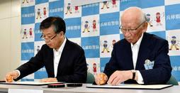 協定書に調印する県交通安全協会の瀧川博司会長(右)と西川直哉本部長=兵庫県警本部