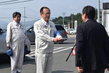 戸羽太市長から親書を受け取り出発する佐藤由也市議会事務局長(中央)と中村吉雄防災対策監(左)