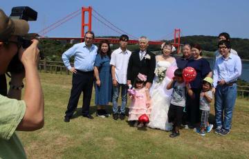 金婚式用の記念撮影に納まる松本さん夫妻(中央)ら=平戸市、平戸大橋公園
