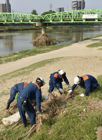 広島県海田町の瀬野川で行方不明者を捜索する消防隊員=20日午前