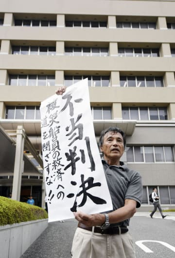 ビキニ被ばく訴訟判決後、高知地裁前で「不当判決」の垂れ幕を掲げる原告側関係者=20日午後