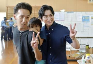 広島市安芸区の避難所を訪問し、写真撮影に応じる「嵐」の松本潤さん(右)=20日午後