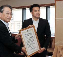 神戸市の玉田敏郎副市長(左)から市スポーツ特別賞の表彰を受ける岡崎慎司選手=神戸市役所