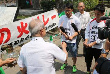 リレーの開始前、トーチに「ナガサキ誓いの火」をともす参加者=長崎市、平和公園
