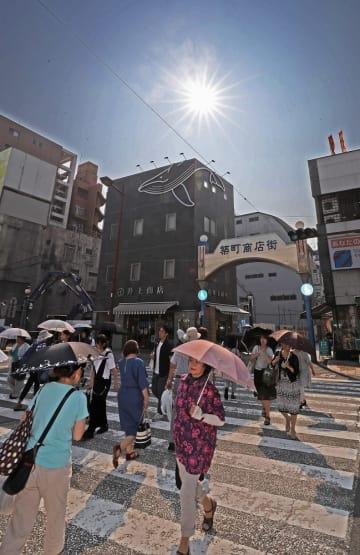 厳しい暑さの中、日傘を差して歩く市民ら=長崎市築町