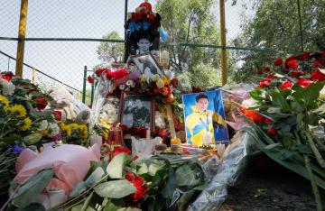 デニス・テン選手を追悼し、捧げられた写真や花束、ロウソクなど=20日、アルマトイ(ロイター=共同)