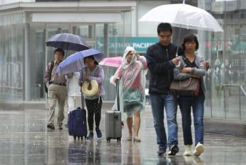 雨の中、うんざりした様子で歩く観光客ら=5日、札幌市中央区