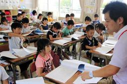 夏休みの過ごし方について話を聞く児童。熱中症対策も学んだ=三田小学校