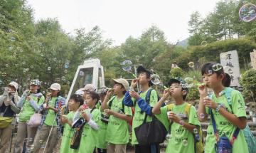 御巣鷹の尾根に登り、慰霊碑前でシャボン玉を飛ばす小学生ら=21日午後、群馬県上野村