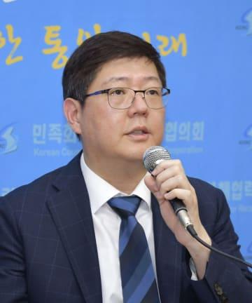 22日、ソウルで記者会見する民族和解協力汎国民協議会の金弘傑代表(共同)