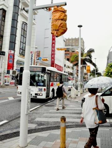 カバーが掛けられた信号機。車は歩行者や周囲の様子を確認しながら交差点に入ってくる=20日、那覇市松尾