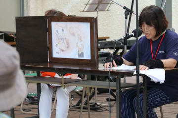 亡き母の戦争、救護被爆体験を紙芝居にして朗読する山下さん(右)=諫早市、ポケットパーク