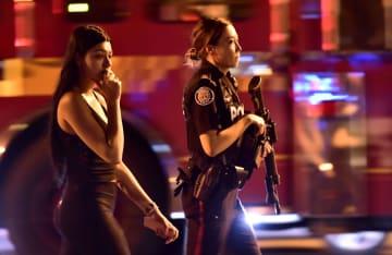 22日、カナダ・トロントで、警察官(右)に付き添われて発砲現場を離れる女性(カナダ通信提供、AP=共同)