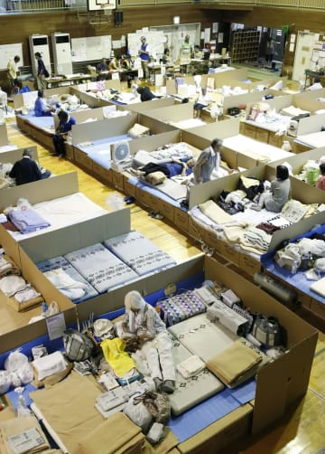 避難所になっている岡山県倉敷市立二万小の体育館で過ごす人たち=23日午後