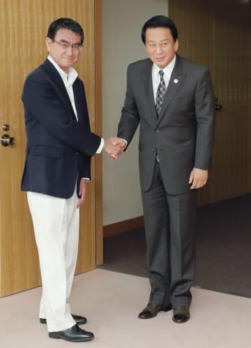 河野外相(左)と握手する杉良太郎さん=23日午後、外務省
