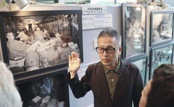 連合国軍占領下の長崎をテーマにした写真展で、来館者に説明をする長崎平和推進協会の担当者=23日午後、長崎市