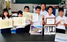 漂着ペットボトルの研究で受賞した多くの賞状を掲げる理科研究部のメンバー=垂水区星陵台4、神戸商業高校